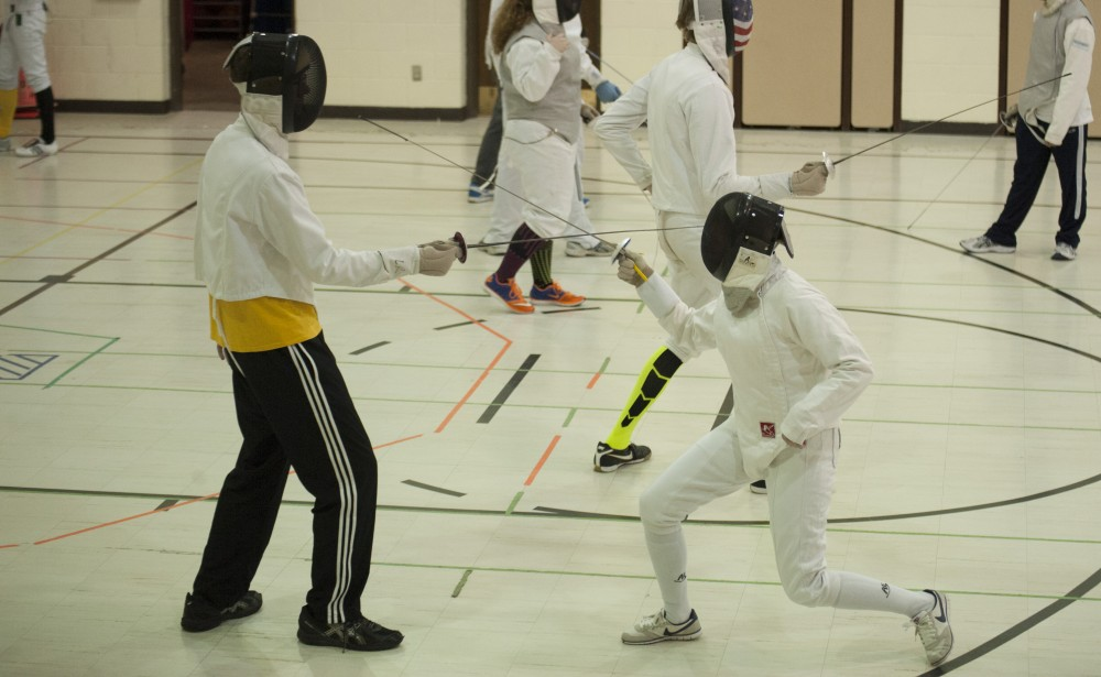 JOSEPH RAVITS | THE SPECTRUM NDSU sophomore Dillon Dee, left and NDSU graduate student Jaime Jensen practice fencing at Grace Lutheran School in Fargo.