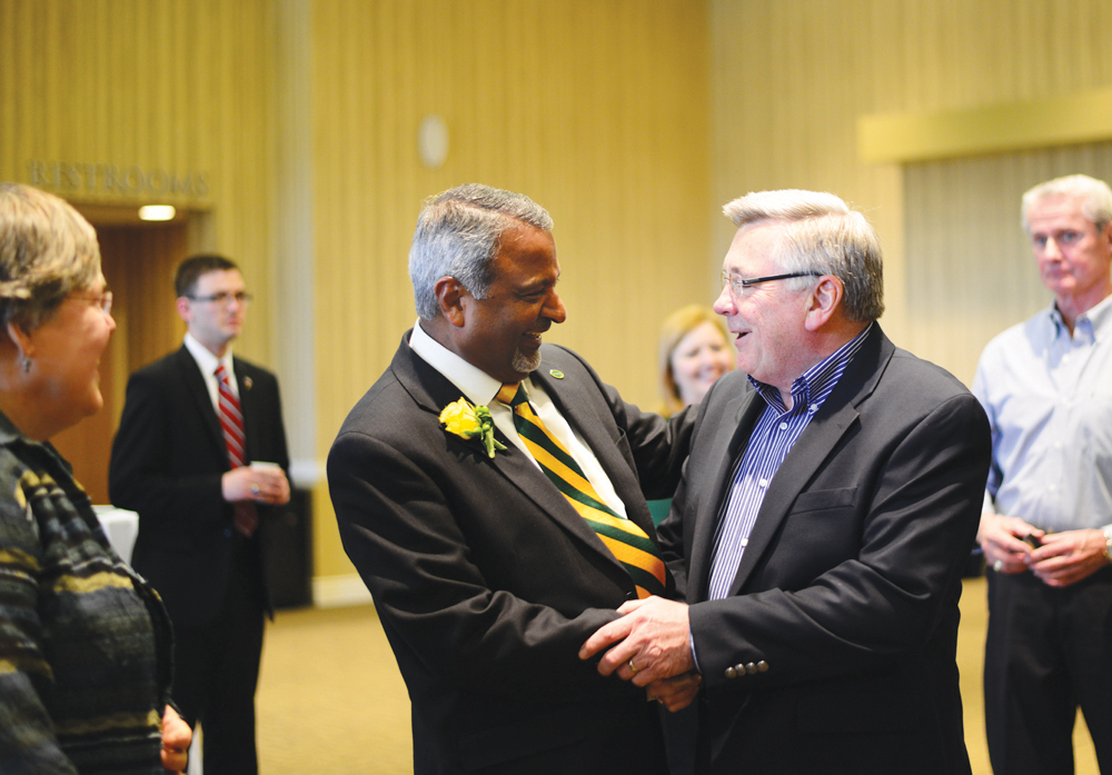 MATAYA ARMSTRONG   THE SPECTRUM Prakash Mathew, left, converses with friends and colleagues at his farewell