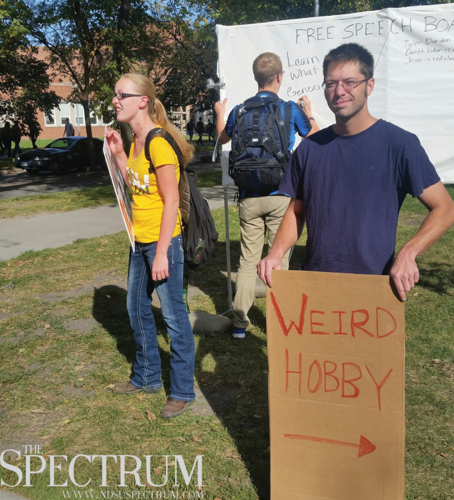 JOSH FRANCIS | THE SPECTRUM Minnesota State University Moorhead senior Brad Wenner holds a sign outside a graphic anti-abortion display on the corner of Centennial Boulevard and Albrecht Avenue Tuesday.