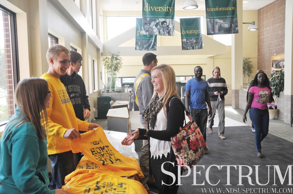 BENJAMIN NORMAN   THE SPECTRUM Jena Sinton buys an NDSU Homecoming T-shirt from student government members Nikki Borstad, Nick Evans and Jacob Dailey on Monday.