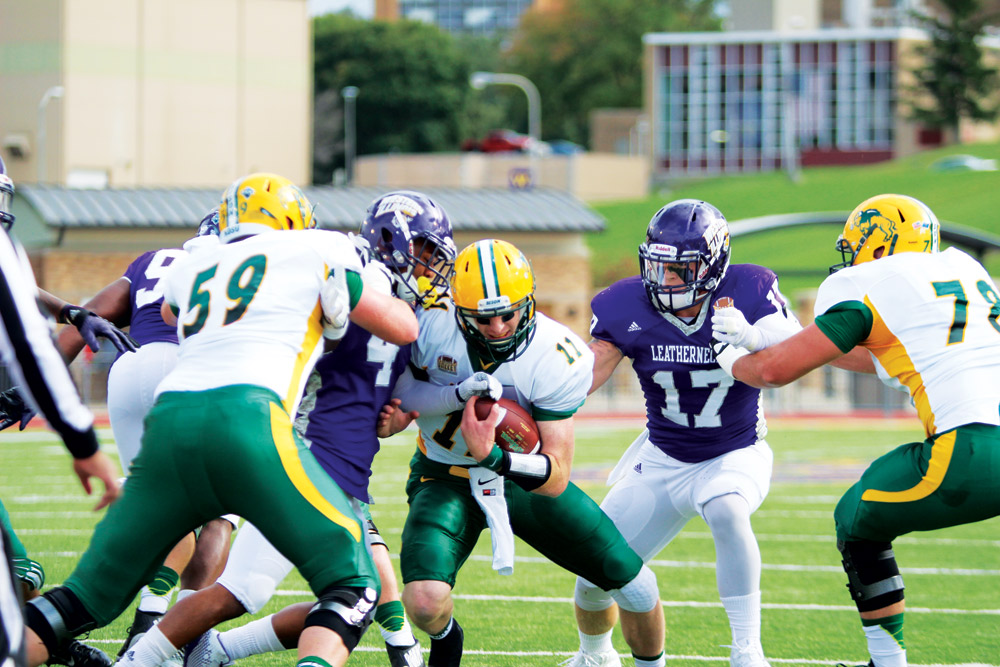 NICHOLAS STEWART | WESTERN COURIER Western Illinois defenders bring down North Dakota State quarterback Carson Wentz Saturday in Macomb, Ill. NDSU came close to being one of the top-ranked Missouri Valley Football Conference teams to be defeated last weekend.